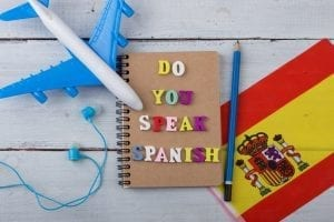 "Concept of learning the spanish language – colorful wooden letters with text ""Do you speak spanish"", flag of the Spain, model airplane, headphones"