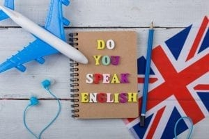 "Concept of learning English language – colorful letters with text ""Do you speak English"", flag of the UK, airplane, headphones"