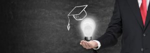 A,Hand,Holding,A,Mortarboard,With,A,Light,Bulb,,Concept